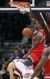 Chicago Bulls' Larry Hughes, right, dunks on Cleveland Cavaliers' Anderson Varejao, from Brazil, during the second quarter of an NBA basketball game T